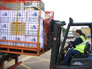 forklift driver removing aquarium stock from large truck